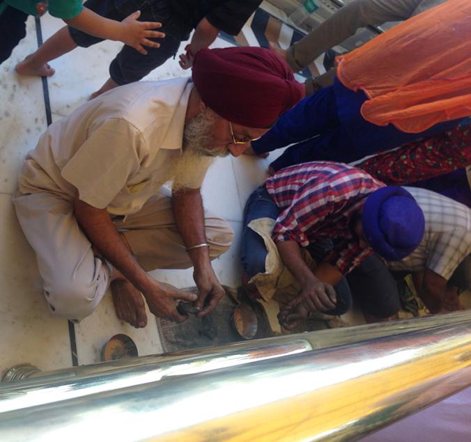 Os devotos sentam no chão para polir o templo